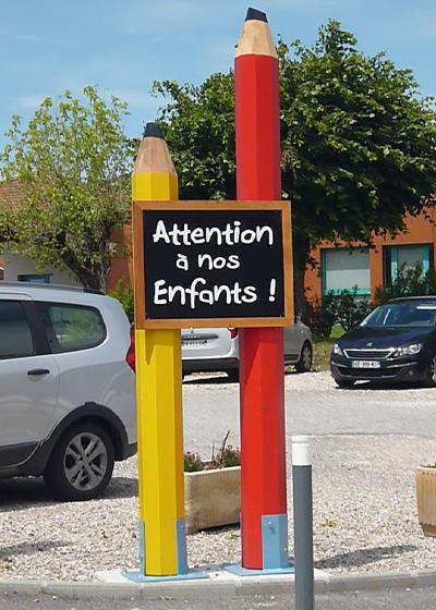 Photo d'un panneau en forme de crayon pour école